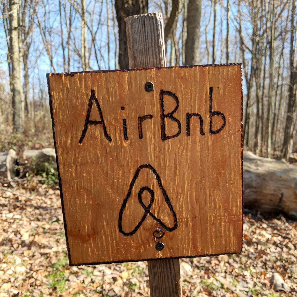 A homemade wood-burned sign welcomes us to the farm