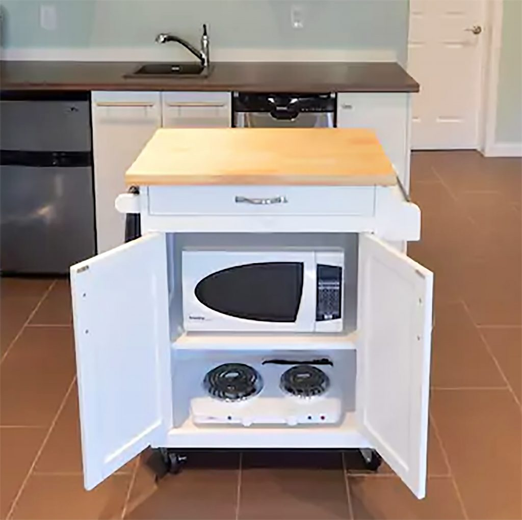 Rolling kitchen island cart with microwave and hotplate stored inside