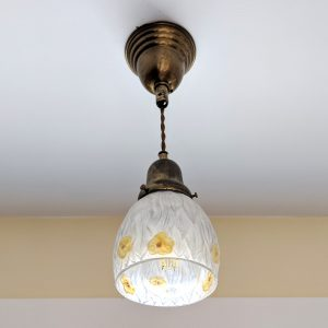 A hanging lamp with yellow flowers etched into the glass shade