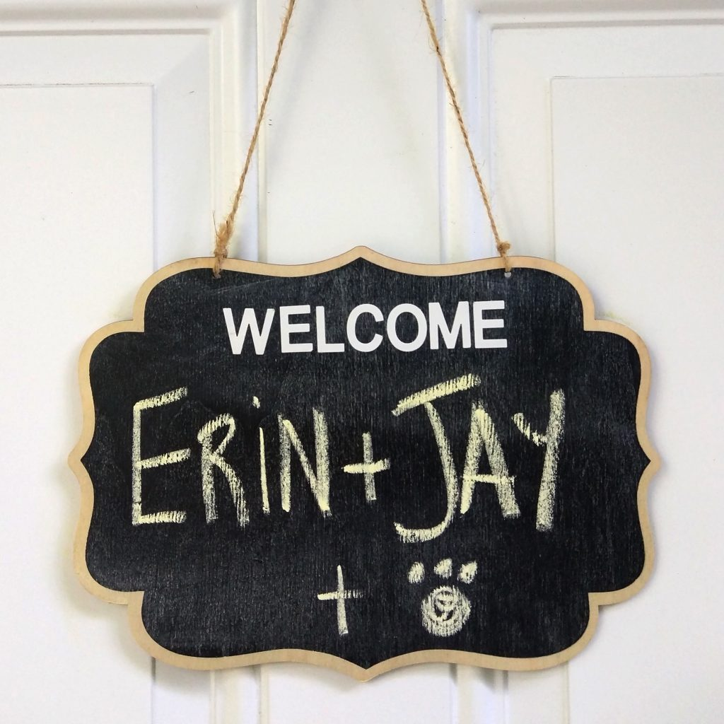 "A sign hangs to welcome us to our new Airbnb home: ""WELCOME! Erin + Jay + Puppy"""