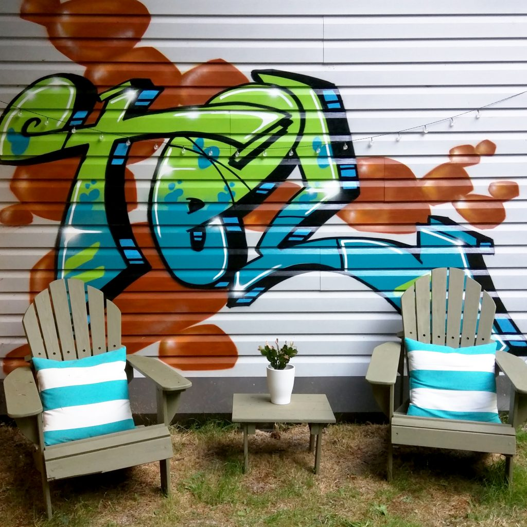 Lawn chairs and graffiti artwork in a private yard
