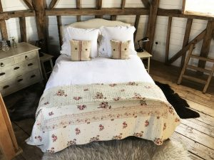 bed with quilt and throwpillows