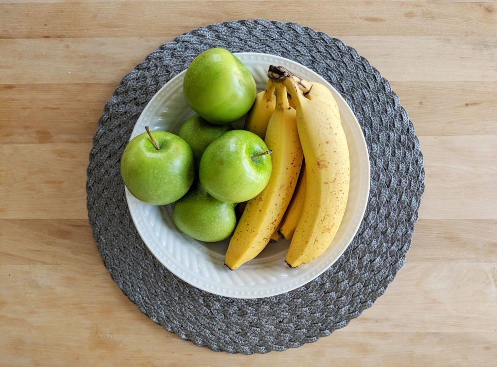 green apples and bananas in a fruit bowl
