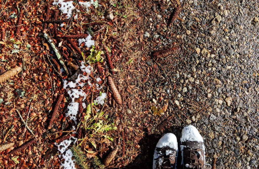 snow covered boots and fall leaves