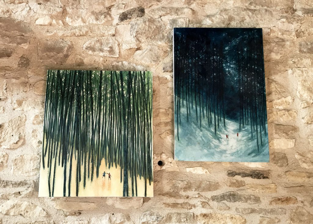 side by side paintings on stone wall