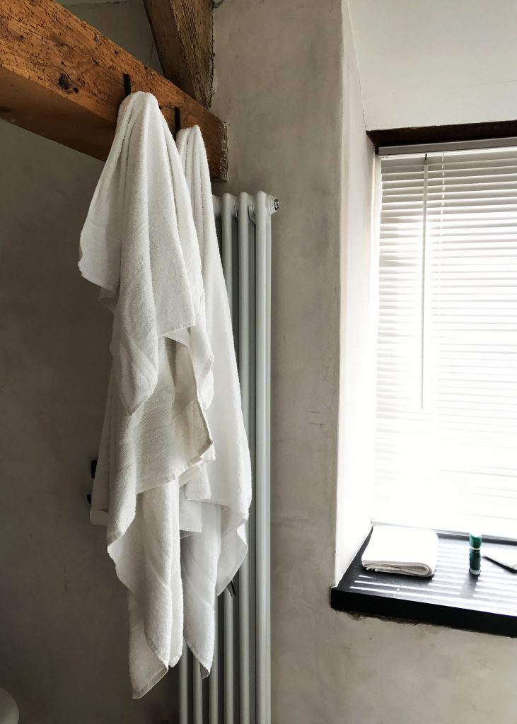 two white towels hanging from exposed wooden bean
