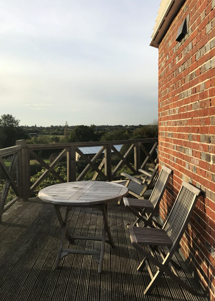 two wooden chairs on beacon hill mill deck in Benenden, England