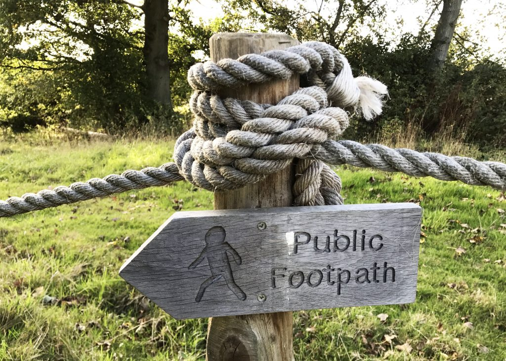 sign for public footpaths cows in countryside pasture in Benenden, England