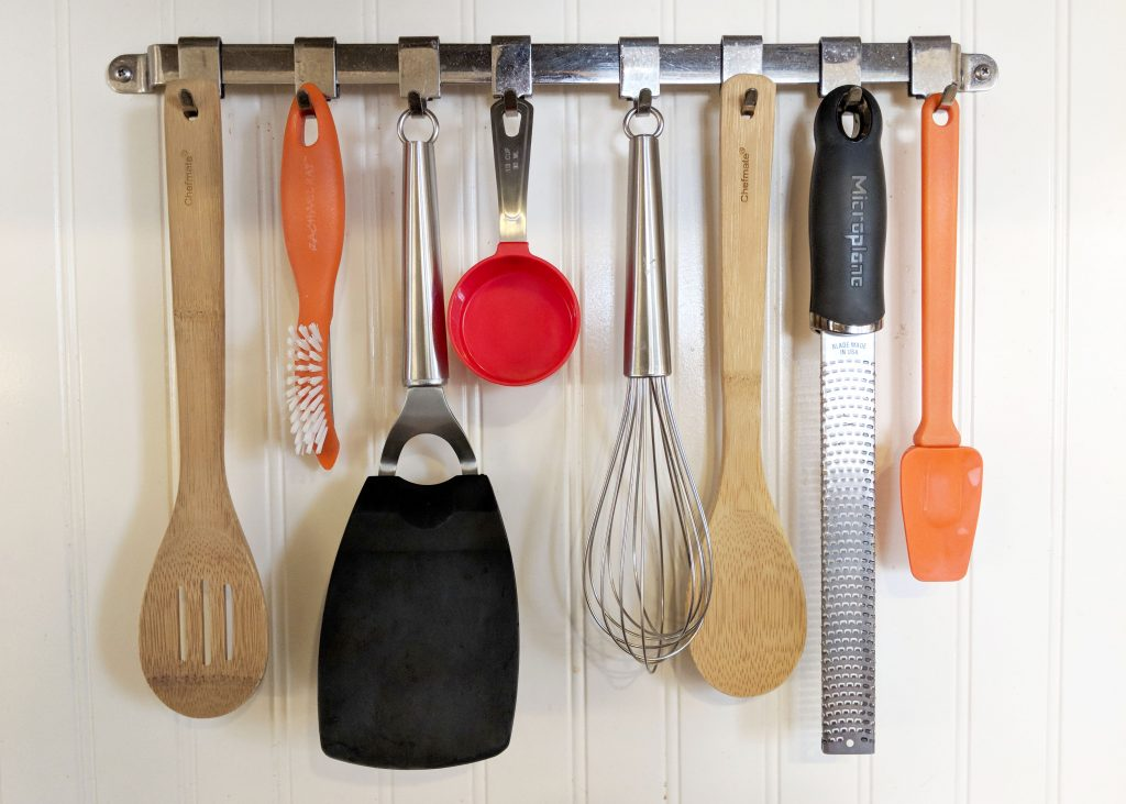 kitchen utensils hanging from a metal rack
