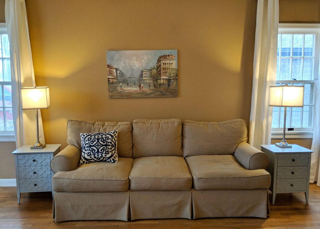 a relaxing living room with a pastel painting of Paris