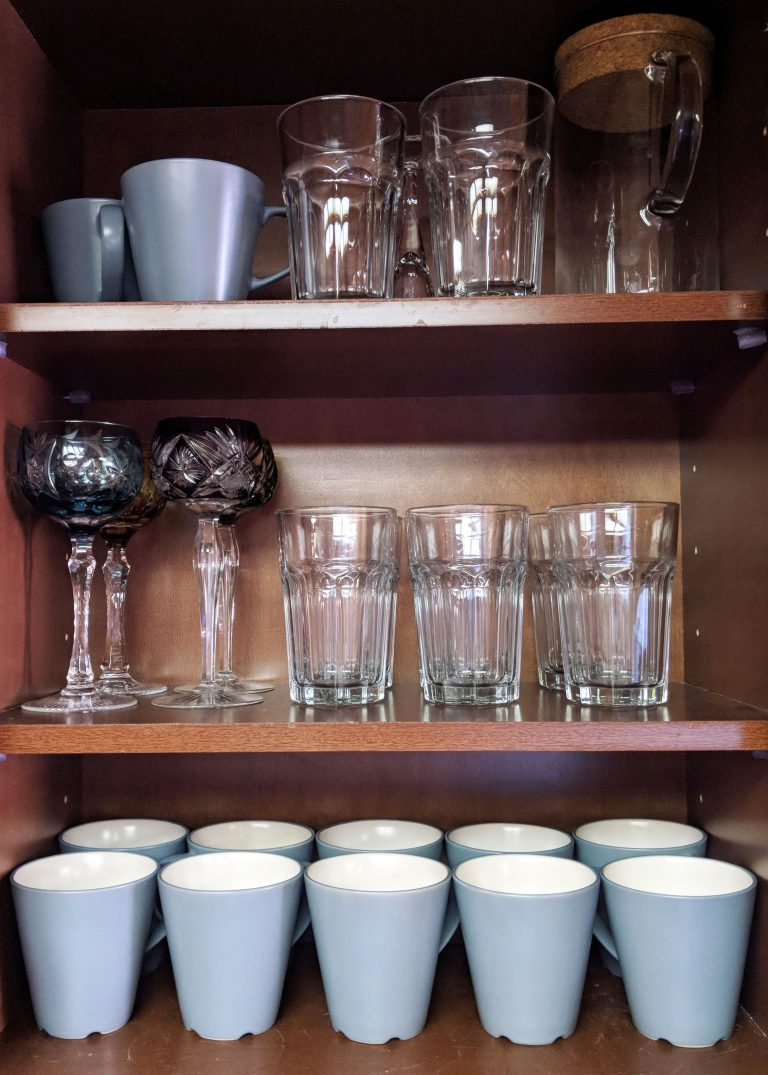 mugs and glasses lined up in a cabinet