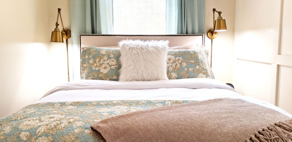 bed with teal quilt and sand colored throw blanket