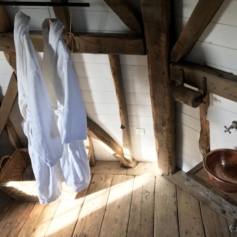 bathrobes hanging in rustic Airbnb bathroom