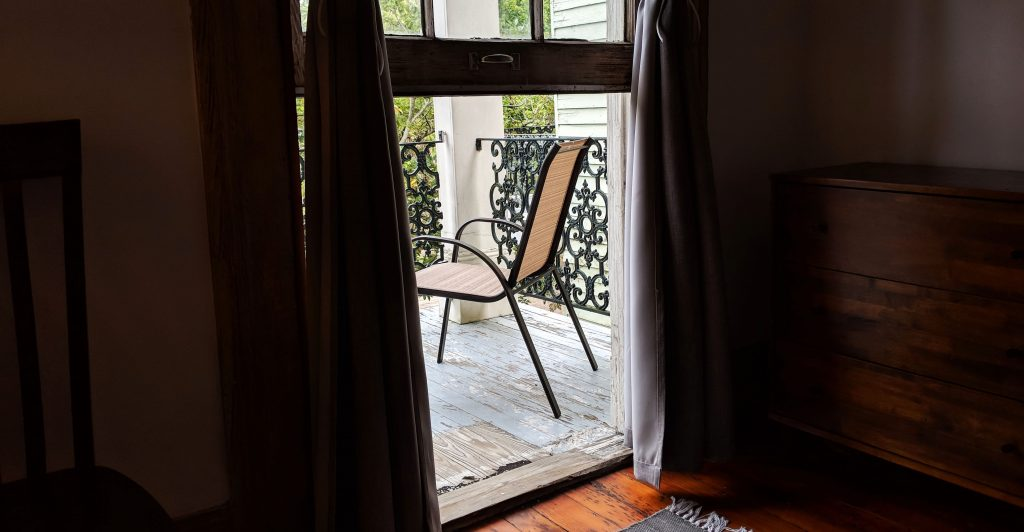 chair through curtains on porch in New Orleans Airbnb
