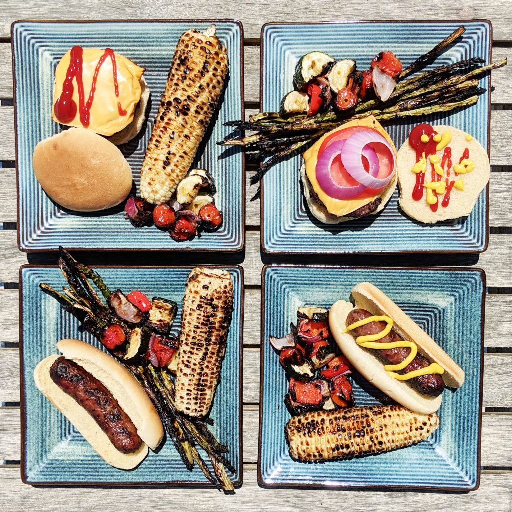 top down view of four plates with grill food